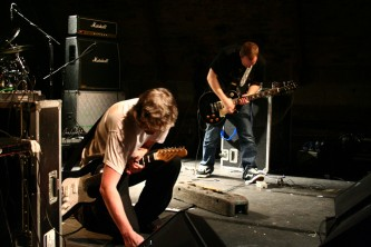 two guitarists looking downwards while playing