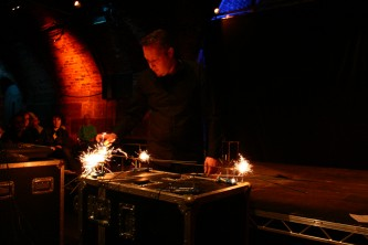 Lee Patterson standing at a table with sparklers burning on stands