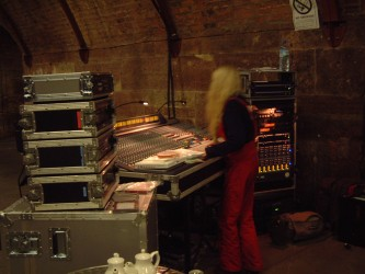 Maryanne Amacher in red dungarees working at a mixing desk