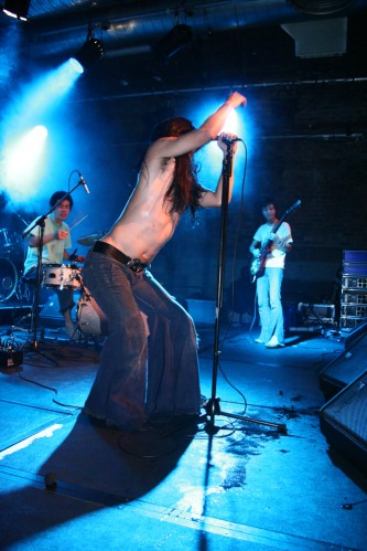 Three men performing rock music, the singer wearing flared trousers