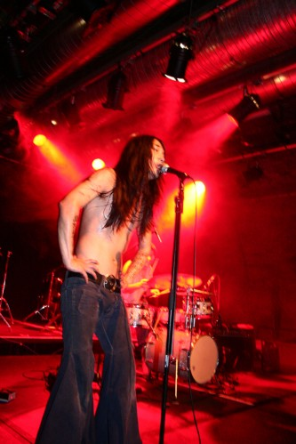Rock pose with large leather belt and sweat covered torso, drums in red light