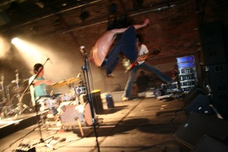 Singer and guitarist are both airborne whilst drummer remains seated