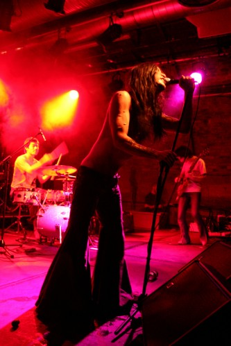 A scarred rock band shot from below with pink light and flared trousers