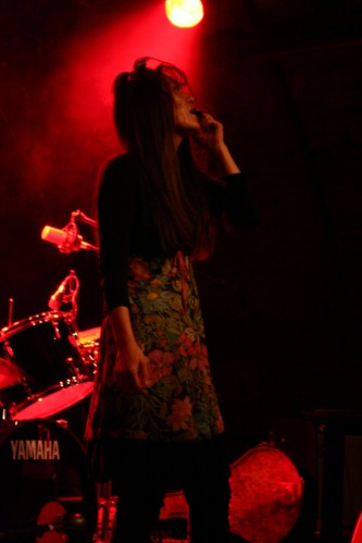 A woman with long hair holds a microphone to her mouth in red light