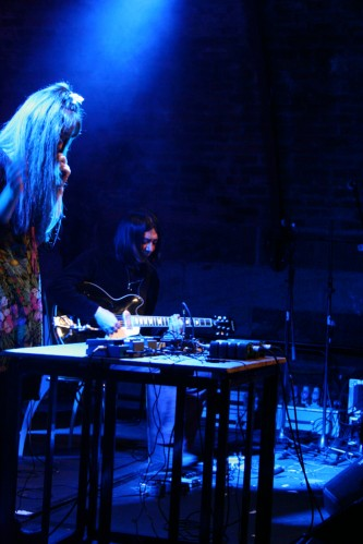 Blue light above a standing woman and a seated guitar playing man