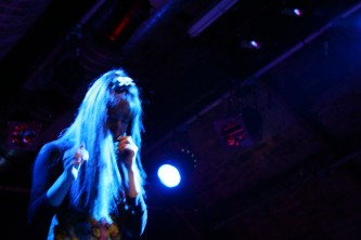 A woman with long hair holds a microphone to her mouth in blue light