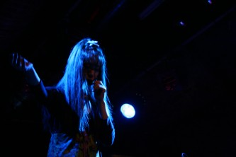 A woman holds her right hand up while singing