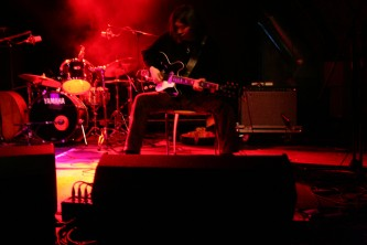 A guitarist sitting in front of equipment legs spread with pink cloud of smoke
