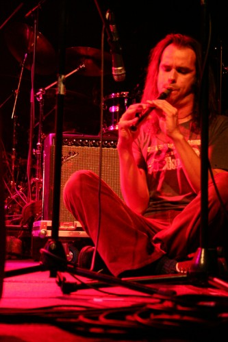 A man sits cross legged playing a small reed instrument