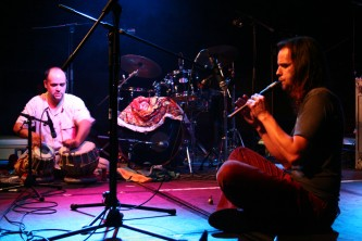 two men seated one playing tabla the other a small reed instrument