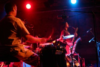 Drummer in foreground, saxophonist in background of stage with spotlights