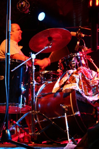Ravi Padmanabha playing drums on stage with a patterned cloth over the bass drum