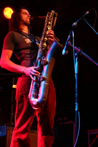 Steve Baczkowskie with baritone saxophone lit from behind