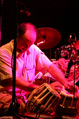A seated man looks down in concentration at some tabla, in pink light