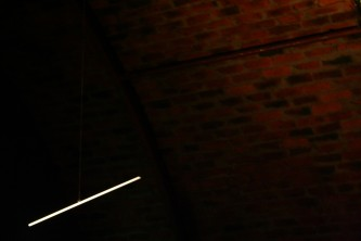 A metal rod suspended in space. light against dark