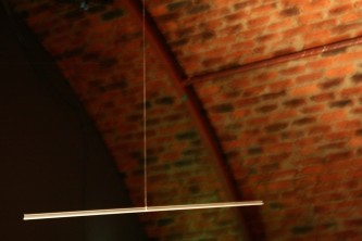 A metal rod suspended in space against a brick arch