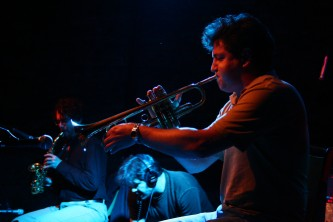 Close up of Greg Kelley playing a trumpet, Bhob and Jason in the background