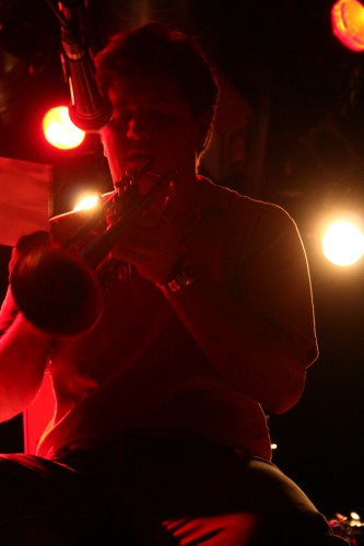 Greg Kelley about to play a trumpet, lit from behind