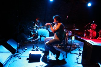 Trio: a man on the floor adjusts a knob, trumpet and sax players on chairs