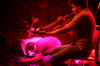 nmperign with jazon lescalleet kneeling. Pink light and wind instruments