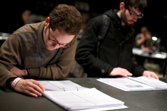 Two people reading documents laid out on a table, both wear glasses