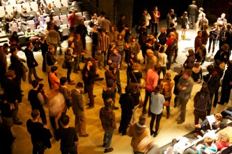 An audience mingle on a floor, taken from above