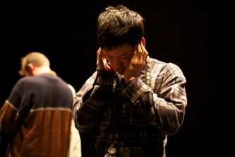 An audience member bows their head with their fingers in their ears