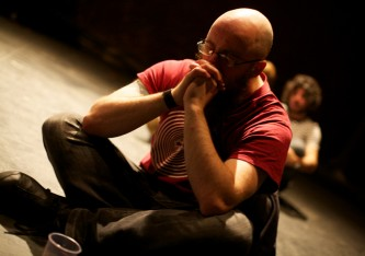 An audience member sits on the floor crossed legged and rests on their hands