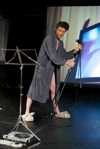 A man in a dressing gown and slippers stikes a pose whilst holding a mic stand