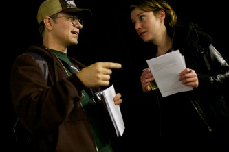 Two people, one in a baseball cap and glasses talk whilst holding handouts