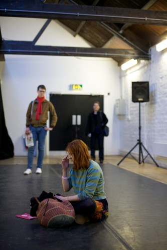 An audience member sits on the floor in a white room with a speaker in the back