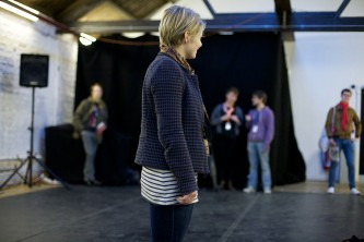 An audience member stands and listens in a room with others and speakers