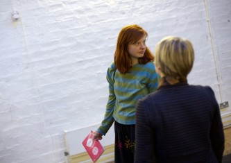 An audience member in a green top holding a programme looks over their shoulder