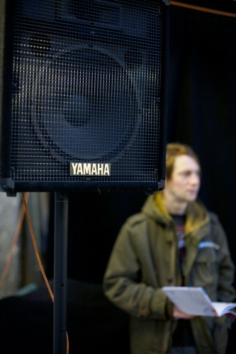 A Yamaha speaker in the foreground, and blurred audience member behind