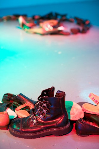 A shot of a black boot on a blue lit floor surrounded by other shoes