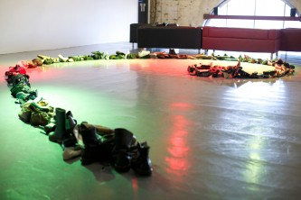 A spiral form made of shoes and boots is laid out on a green and red lit floor