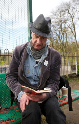 Tam Dean Burn reading on a bench somewhere in Glasgow
