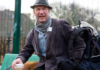 Tam Dean Burn broadcasting from a bench with coffee and a hat