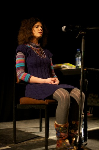 A woman with curly hair sits on a chair as she sings