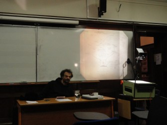 Jean-Luc Guionnet sitting behind a desk looking dishevelled