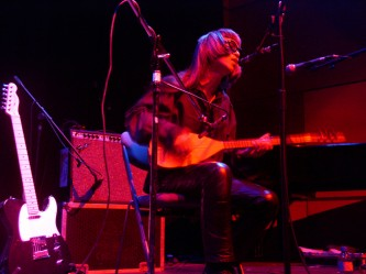 Keiji Haino seated playing a saz in pink light