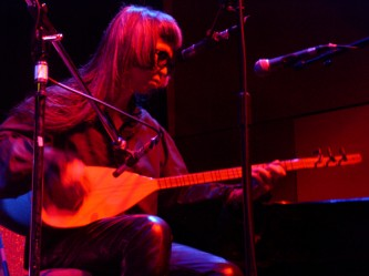 Keiji Haino seated playing a saz, close up in pink light