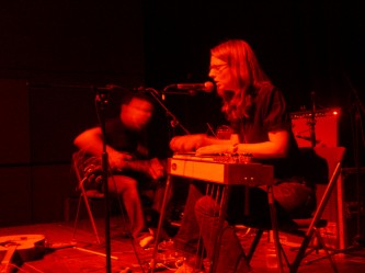 Two people playing electric guitar and lap steel guitar respectively, red light