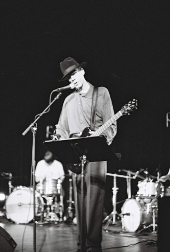 Jandek with two drummers on stage in Austin