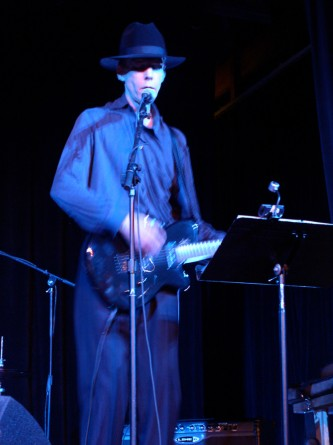 Jandek playing an electric guitar on stage in Austin