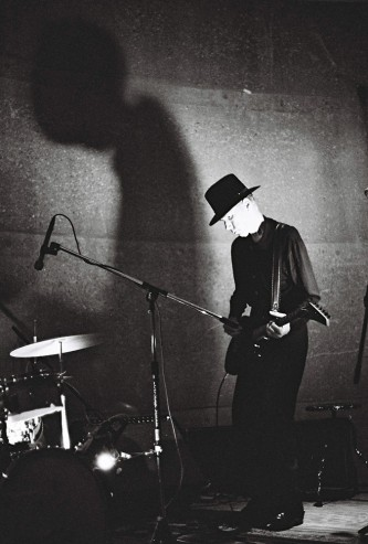 Jandek playing an electric guitar near a shadow