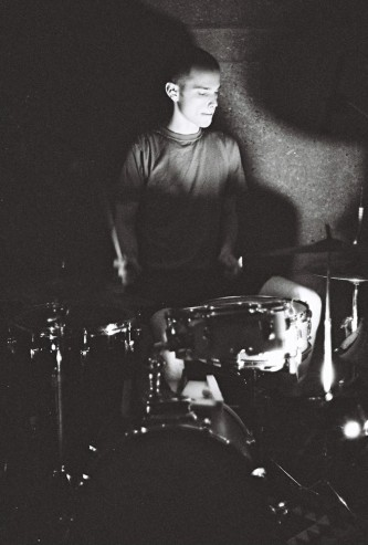 Chris Corsano angelic behind a drum kit cymbal shadows on either side