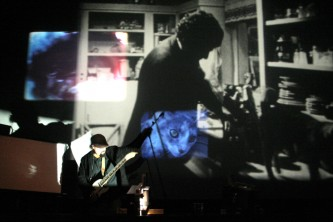 Andrew Lampert in front of projections playing a guitar