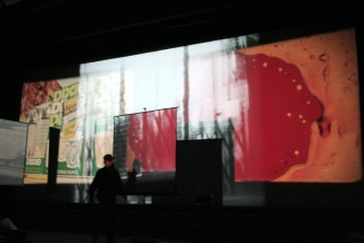 Andrew in silhouette in front of a multi screen projection