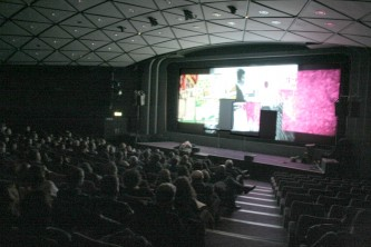 wide angle shot of theatre space with audience and many screens